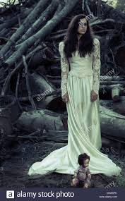 woman in antique wedding dress with cut down trees and creepy doll