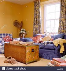 painted chest and blue sofa in yellow coastal living room with