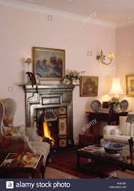 Wing Chairs For Living Room by Wingback Chair Beside Victorian Cast Iron Fireplace In Small