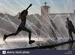 cool hoses teenagers jumping through water fountains splashing from fire hoses