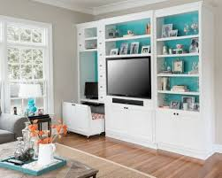 teal accent wall color using white wooden built in shelving units