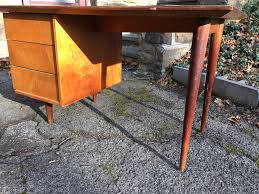 mid century desk with long legs attainable vintage
