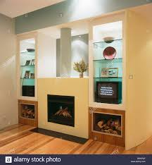logs stored on either side of modern fireplace in wall with