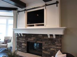 sliding doors over tv above fireplace fireplace pinterest