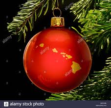 a red bauble with the golden shape of hawaii hanging on a