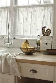 kitchen white curtains that adorn lower half of glass windows in