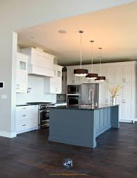 open layout kitchen with white cabinets gray island cambria