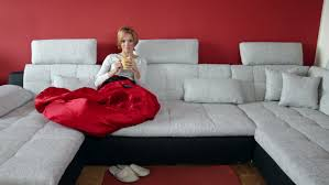Huge Sofa Bed by Happy Young Woman Lying On Sofa And Reading Book Stock Footage
