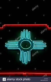 the mexico zia sun symbol glows in neon against the sky