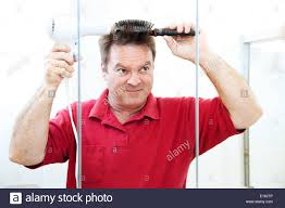 man blow drying his hair in the bathroom mirror stock photo
