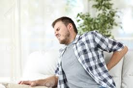 canap mal de dos un malheureux souffrant de mal au dos assis sur un canapé dans le