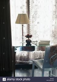 cream lamp on mirrored desk in front of window with lace curtains