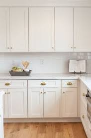 white shaker cabinetry with brass cups and knobs by rafterhouse