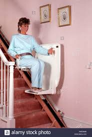 middle age aged woman female using stair chair lift elevator in