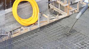 pouring concrete mix from cement mixer on concreting formwork