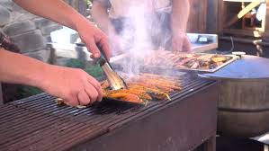 grillk che fraying fish on the grill chef turns the fish that is roasted on