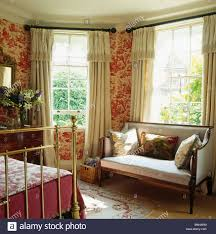 red toile de jouy wallpaper in bedroom with antique sofa in front