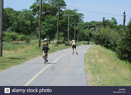 2 two people one bike and one rollerblading on bike path at cape