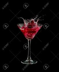 cocktail splash red martini cocktail splashing into glass on black background
