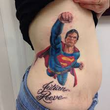 art superman portrait tattoo on ribs of a lovely girly