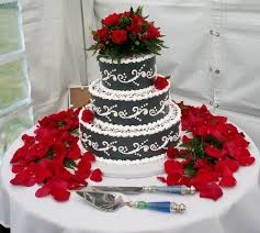a dramatic statement black wedding cake with fresh red roses