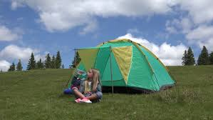 Camping In The Backyard Little Boy Playing With Garden Sprinkler And Umbrella In The