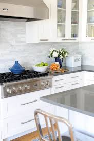 hamptons style white kitchen with shaker cabinets marble splashback
