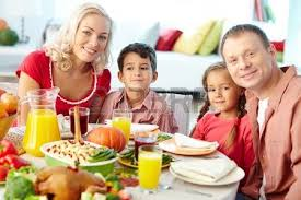happy family sitting by festive table and traditional