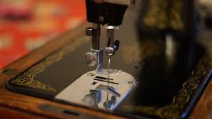 worker makes seams on leather material by sewing machine in