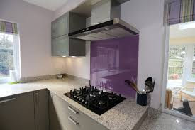 contemporary modern shiny grey kitchen with purple splashback and