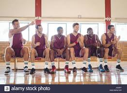 basketball player on bench excited basketball player sitting on bench in court stock photo
