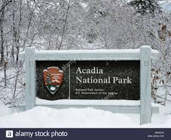 sign at an entrance to acadia national park in the winter acadia