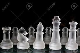 a frosted glass chess set on a glass chess board with a dark