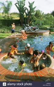 kids playing in backyard swimming pool during birthday party in