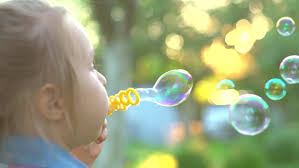 happy child blowing soap bubbles in park motion stock
