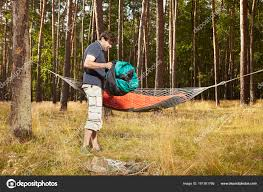 man in wild forest hanging hammock bed with mate and sleeping bag