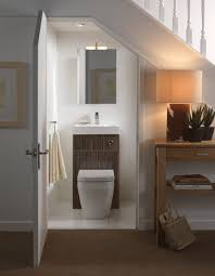 small basement bathroom with vanity plus mirror under staircase