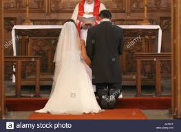 wedding help groom with help written on soles of shoes kneels at altar during