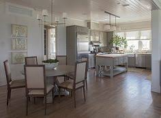 White Kitchen Cabinets With Light Hardwood Floors And Brass