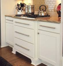 white shaker cabinets with slab drawer fronts used to create a