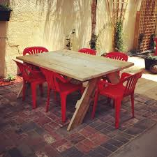 recycled pine wood patio table and plastic lawn chairs painted red