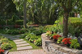 a summer view of an ornamental garden with a slate pathway and