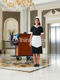 uniforme femme de chambre hotel standing by cleaning trolley in hotel foyer smiling portrait