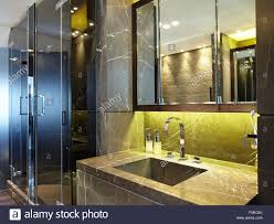 interior dark marble bathroom with basin mirror and glass shower