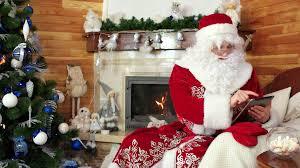 santa claus using gadget saint nicolas sitting in chair with