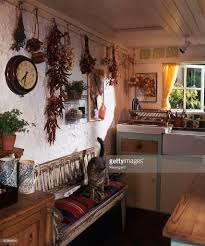 country kitchen with dried flowers and herbs hanging on wall and a
