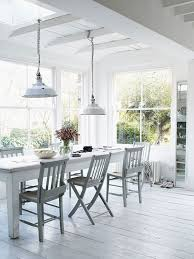 white dining room with industrial pendant lights and long plus