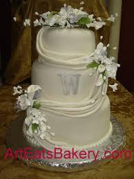 three tier fondant draped wedding cake with silver monogram and elegant sugar flowers jpg
