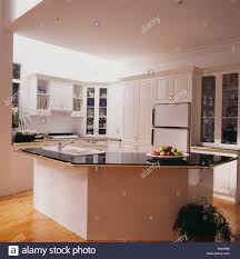 black granite worktop on island unit in modern white kitchen stock