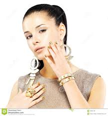 woman with golden nails and beautiful gold jewelry royalty free